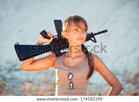Young beautiful female soldier dressed in a camouflage with a gun in the outdoor