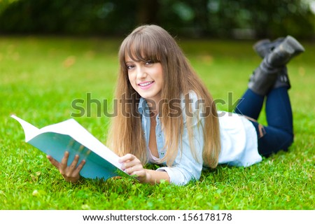 Young beautiful female student reading a book on the grass  - stock photo