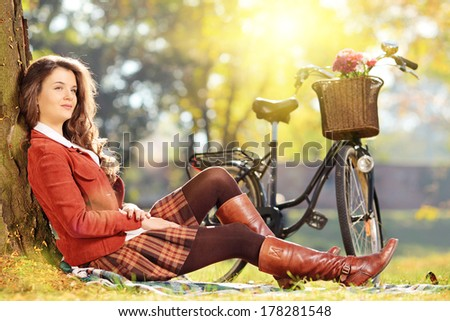 Young beautiful female with bicycle relaxing in a park - stock photo