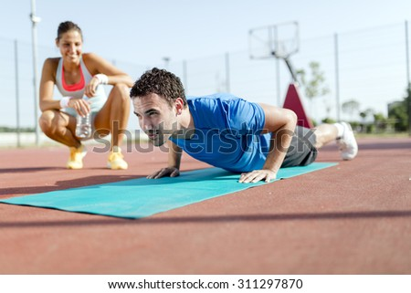Young, beautiful, fit and healthy personal trainer counting push-ups and motivating - stock photo