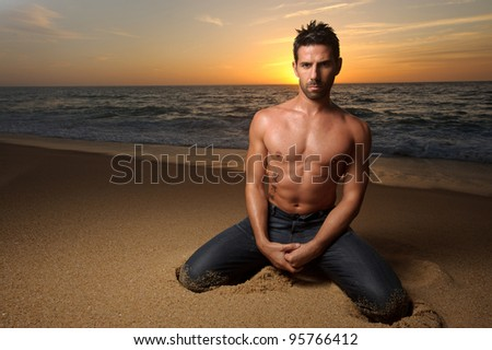 young beautiful fit man at the beach with sunset on his back - stock photo
