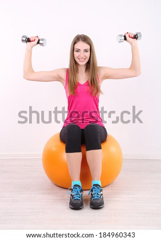 Young beautiful fitness girl exercising with orange ball and dumbbells in gym