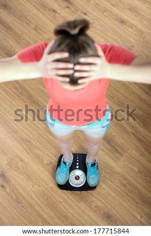 Young beautiful fitness girl standing on weight - stock photo
