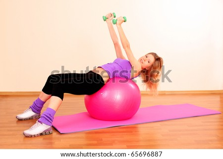 Young beautiful fitness girl with pink ball exercising  in the gym