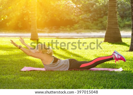 Young beautiful fitness girl with ponytail do exercises on green grass at the park. Healthy lifestyle and sport concept - stock photo