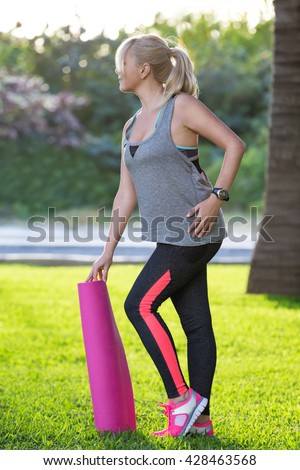Young beautiful fitness girl with ponytail holding pink mat and ready for doing exercises.  Healthy lifestyle and sport concept - stock photo