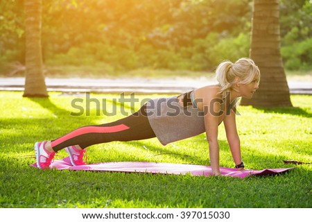 Young beautiful fitness woman with ponytail doing plank position outside on the green grass at the park