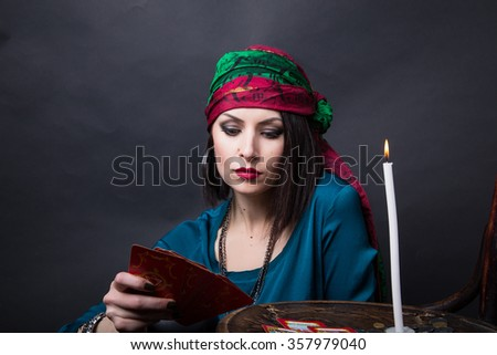 Young beautiful fortune teller wondering on the Tarot cards. Predicting the future, access to the astral