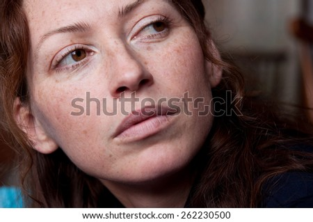 young beautiful freckled woman without makeup brown eyes looking back - stock photo