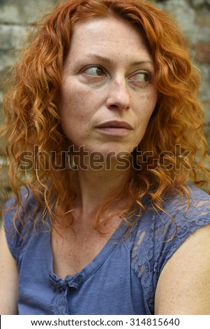 young beautiful freckled woman without makeup looking over her shoulder in blue lace tshirt  - stock photo