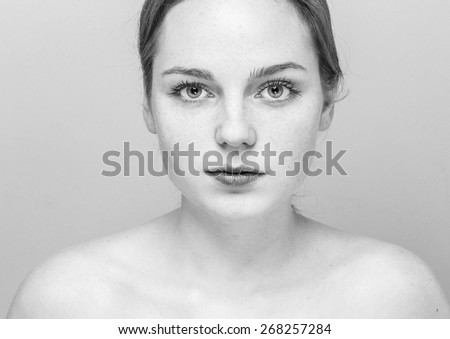 Young beautiful freckles woman face portrait with healthy skin black and white - stock photo