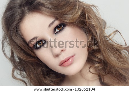 Young beautiful fresh girl with curly hair and smoky eyes - stock photo