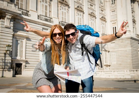 young beautiful friends tourist couple visiting Madrid - Spain on holidays exchange students posing together in town happy with city map on sunny day in travel and vacation concept - stock photo