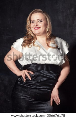Young beautiful full-bodied blonde woman in a black and white vintage dress - stock photo