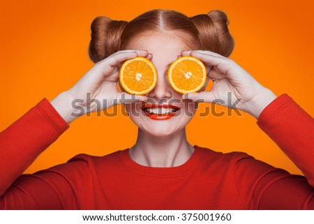 Young beautiful funny fashion model with orange slice on orange background. with orange makeup and hairstyle and freckles. holding orange between eyes with toothy smile. - stock photo