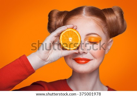 Young beautiful funny fashion model with orange slice on orange background. with orange makeup and hairstyle and freckles. holding orange between eyes with nice smile. - stock photo