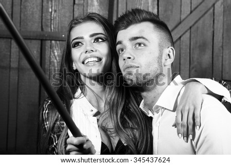 Young beautiful funny happy smiling couple making faces for taking selfie photo with long monopod looking at camera posing in studio on wooden backdrop black and white, horizontal picture - stock photo