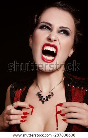 Young beautiful furious vintage woman with vampire fangs crying - stock photo