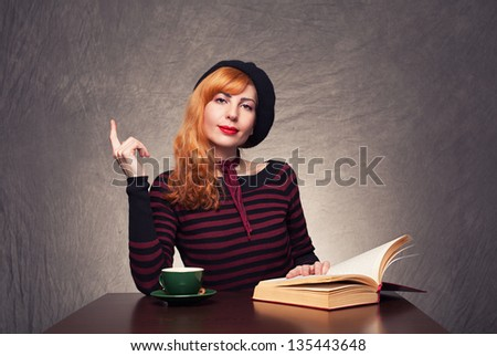 young beautiful ginger lady showing something with her finger on grunge background - stock photo