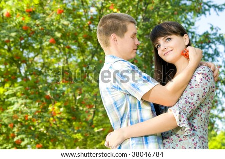 Young beautiful girl and the guy, embrace under a bush of a mountain ash, a happy smile.