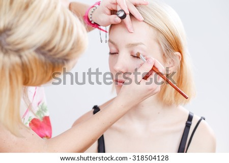 Young beautiful girl applying make-up by beautician artist - stock photo