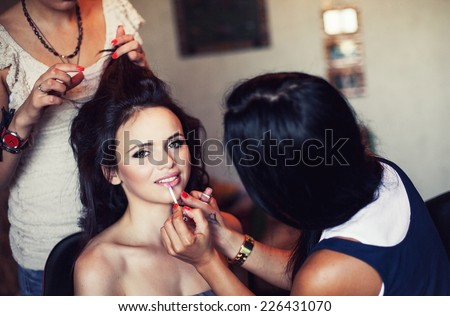 Young beautiful girl applying make-up by make-up artist - stock photo