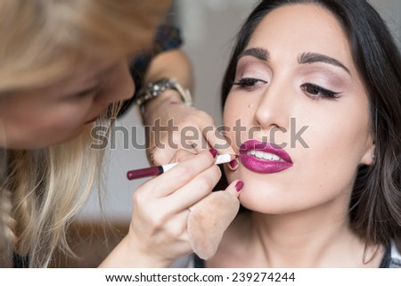 Young beautiful girl applying make up by makeup artist - stock photo