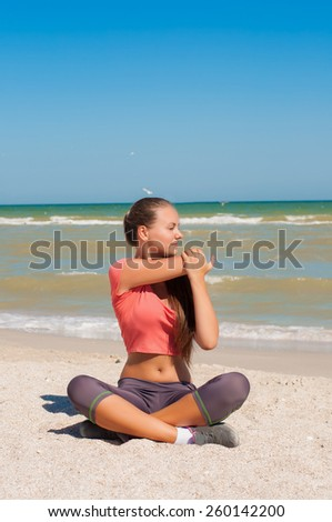Young beautiful girl athlete playing sports on the beach in summer - stock photo