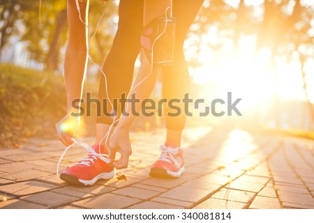 Young beautiful girl athlete with armband and earphones listening to music and tying laces during training with sunset and sunbeam on background. Copy space. Bright and warm photo - stock photo