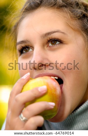 Young beautiful girl bites an apple.