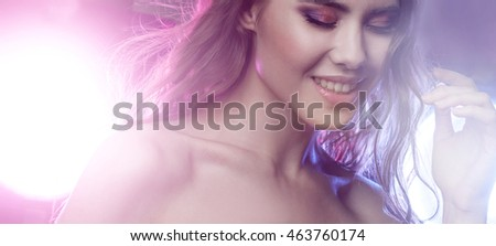 Young beautiful girl brunette, amid spotlight. Night club, dance culture. Effect of illumination
