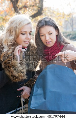 Young beautiful girl brunette and blonde  with shopping - stock photo