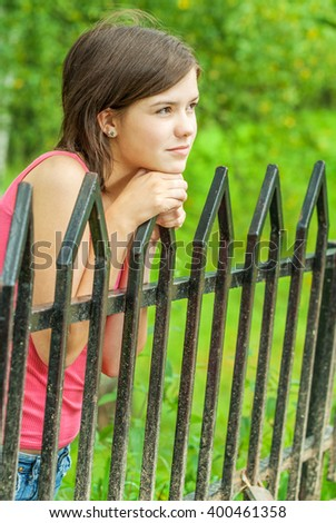 Young beautiful girl costs on bridge and keeps for its handrail. - stock photo