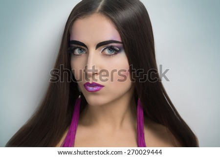 Young beautiful girl. Creative style. Holidays, party, disco, club. Glowing eyes, gorgeous smile. Bright makeup, long eyelashes, expressive eyebrows, purple lips, perfect face, fashion accessories  - stock photo