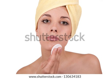 Young beautiful girl does cosmetic cream in the bathroom