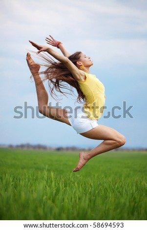 Young beautiful girl doing gymnastic jumps outdoors - stock photo