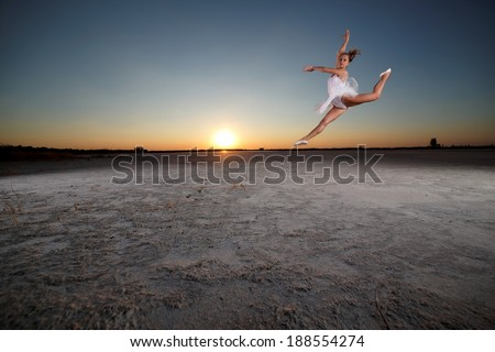 Young beautiful girl doing gymnastic jumps outdoors at sunset. - stock photo