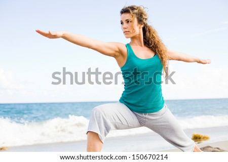 Young beautiful girl doing yoga on the beach in warrior pose stock