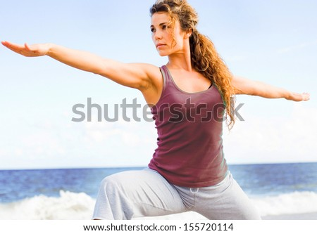 young beautiful girl doing yoga on the beach in warrior pose. - stock photo
