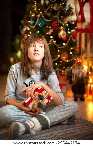 Young beautiful girl dreaming about christmas miracles sitting near new-year illuminated tree.  - stock photo