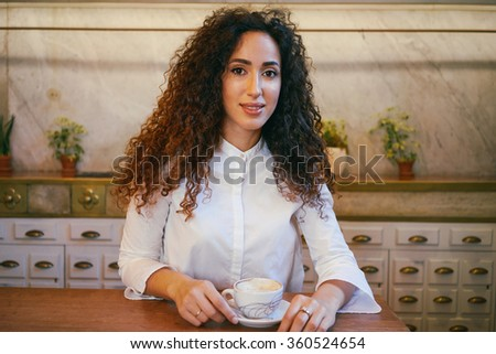 young beautiful girl drinking coffee in a cafe.attractive girl with long curly hair drinking coffee in a coffee-shop and smiling at the camera - stock photo