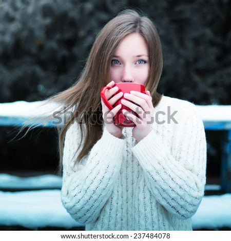 Young beautiful girl drinking tea in a cool winter park  - stock photo