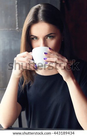 Young beautiful girl drinking tea in cafe, holding cup both hands and thoughtfully looking at camera. Girl enjoying her leisure time alone in coffee shop cafe. Girl with green eyes in black t-shirt. - stock photo