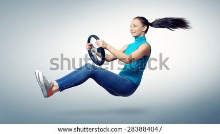 Young beautiful girl driver with a wheel, auto concept