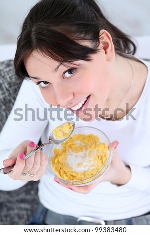 Young beautiful girl eating cornflakes, healthy breakfast - stock photo
