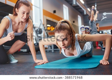 Young, beautiful girl encouraged by friends when doing push-ups in the gym