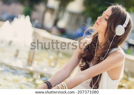 Young beautiful girl enjoying her music listening to a set of earphones attached to her tablet computer on the street - stock photo