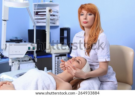 Young beautiful girl getting spa treatments. Doctor doing massage of the face. - stock photo