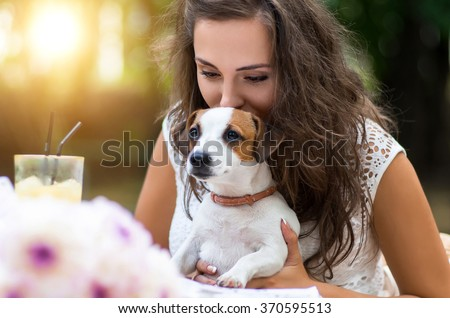 Young, beautiful girl has received a long-awaited gift-dog breed Jack Russell Terrier. She  happiness and love  animals.Girl sitting at a restaurant or cafe table outdoors. Flowers on the background.