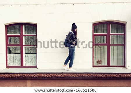 Young beautiful girl hipster walking on cornice of house. Outdoors - stock photo